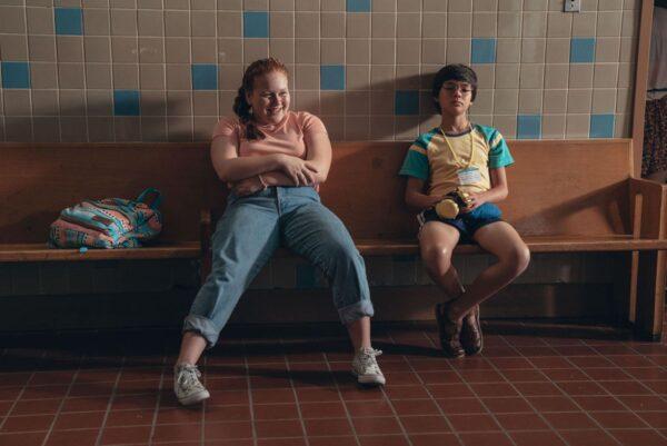Dwójka dzieci siedzi na ławce. Pomieszczenie wyłożone płytkami. Pyzata dziewczyna uśmiechnieta. Drobny chłopiec zamyślony.