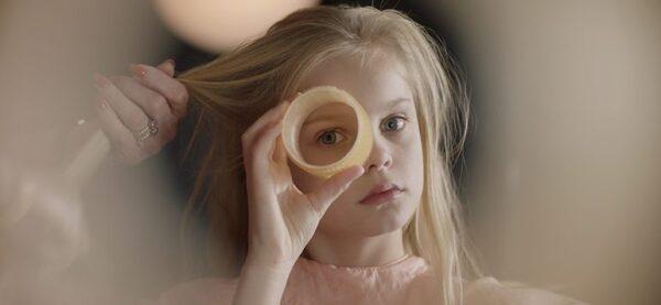 Dziewczynka o blond włosach. Kobieca dłoń je czesze. Dziewczynka jedno okiem spogląda przez okrągły wałek do włosów.